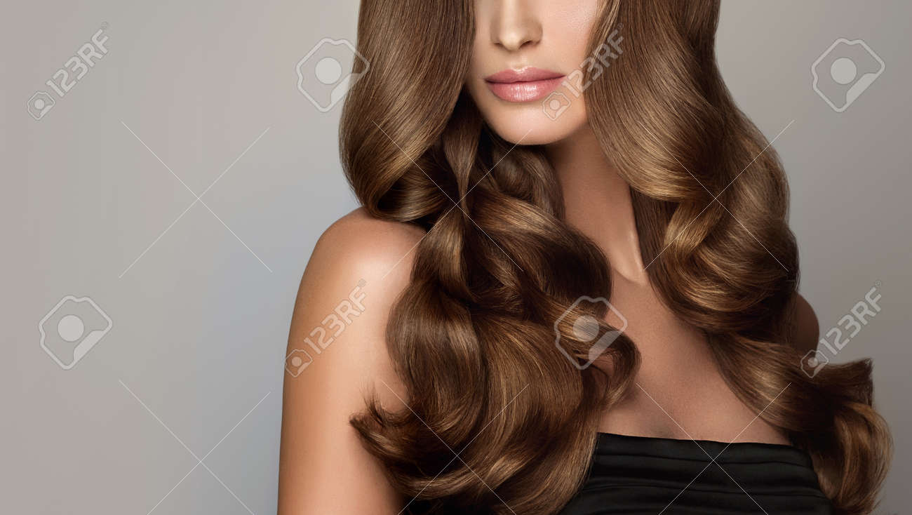Young, brown haired woman with voluminous hair. Beautiful model with long, dense and curly hairstyle and vivid make-up. Perfect hair. Incredibly dense, wavy,and shiny hair. - 92992300