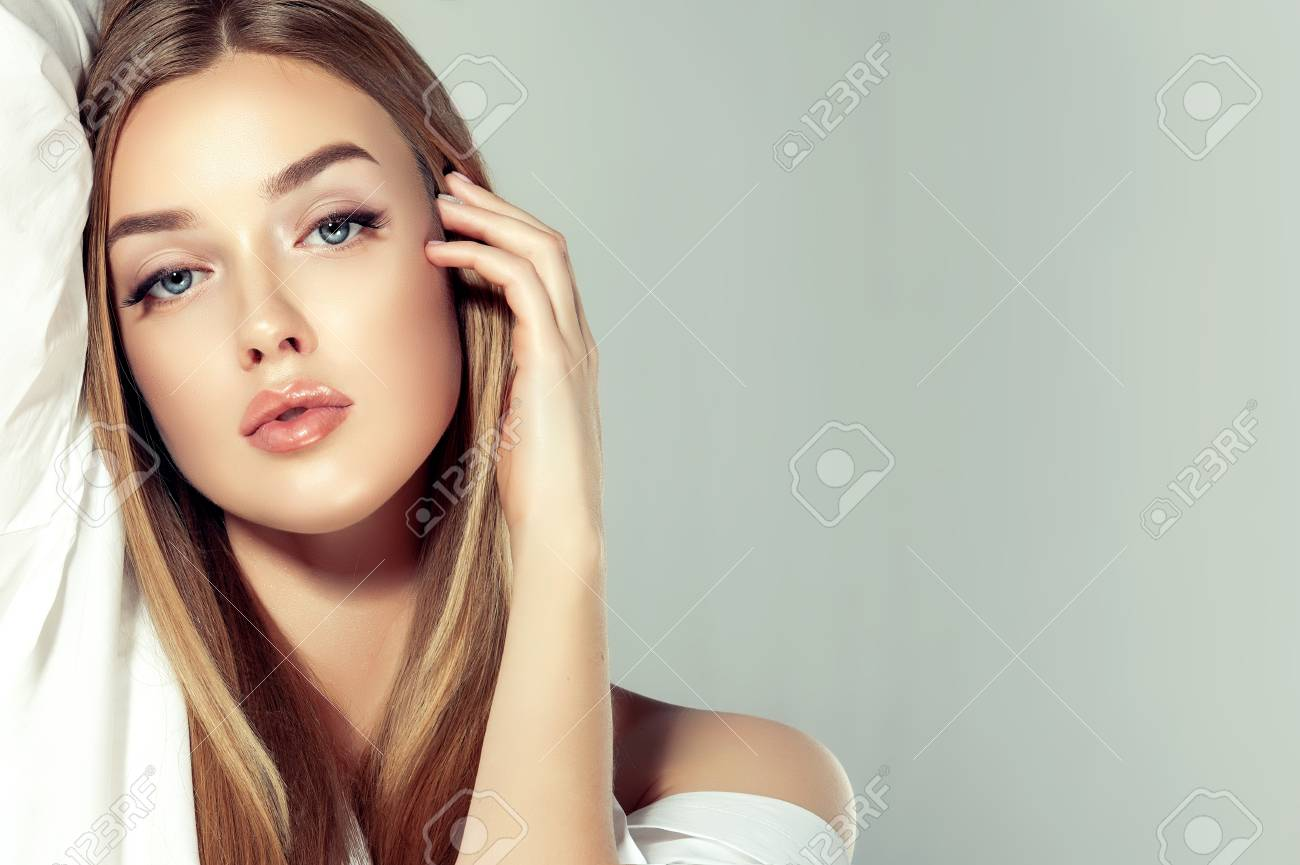 Young Gorgeous Woman With A Freely Lain Long Straight Hairstyle