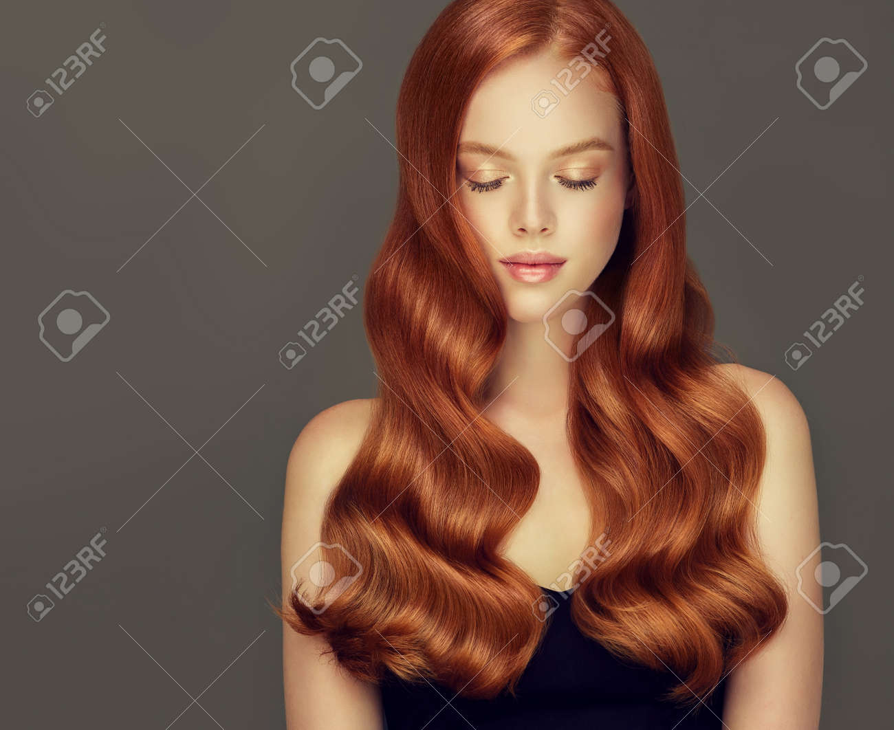 Young, red haired beautiful model with long, curly, well groomed hair. Irish beauty. Excellent hair waves. Hairdressing art and hair care. - 114695652
