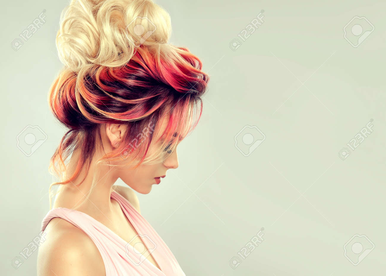 Young attractive woman is demonstrating multi colored hair gathered in elegant evening or wedding hairstyle. Hairdressing art and coloration of hair. Portrait in profile. - 121942061