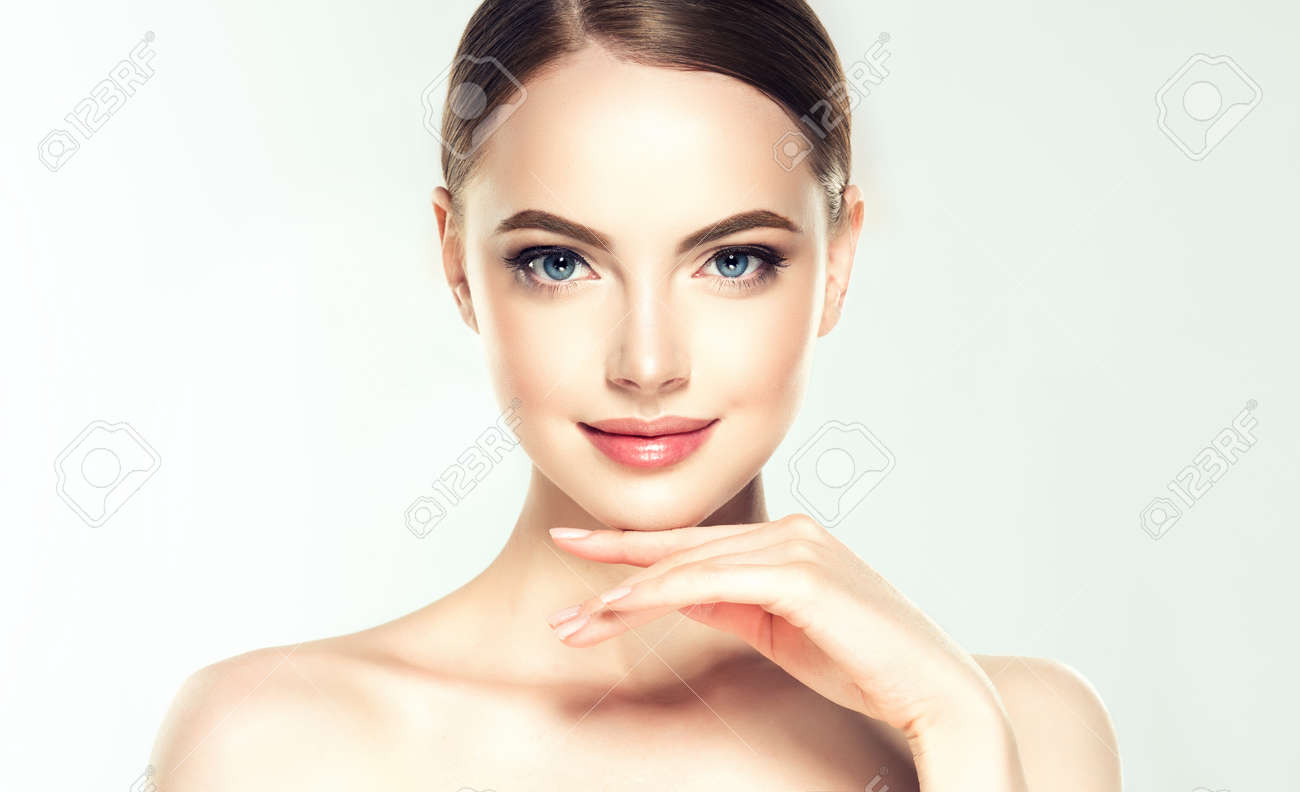 Gorgeous, young woman with clean, fresh skin is touching own face. Soft make up and light smile on the perfect face.Facial treatment. - 124699086