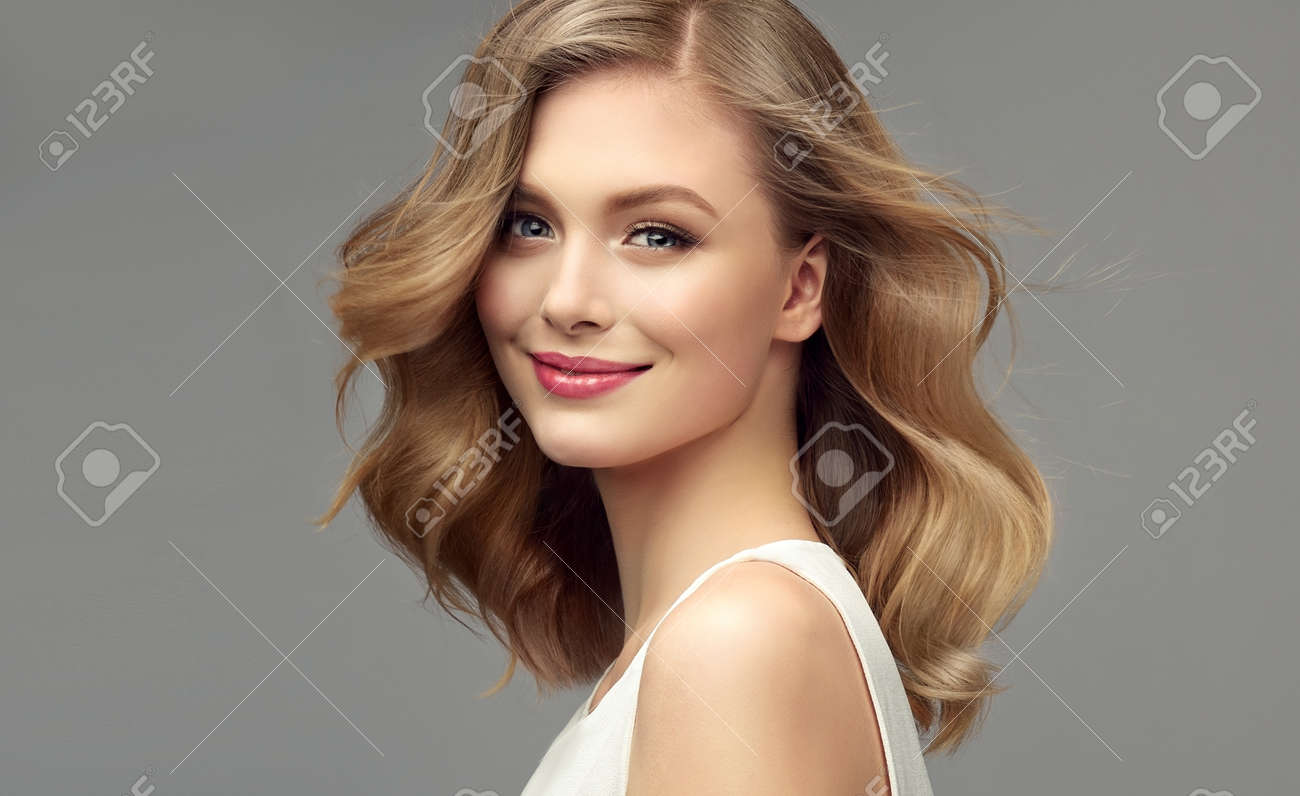Model with dark blonde hair. Frizzy, elegant hairstyle is surrounding lovely face of tenderly smiling young woman. Hair care and hairdressing art. - 133213399