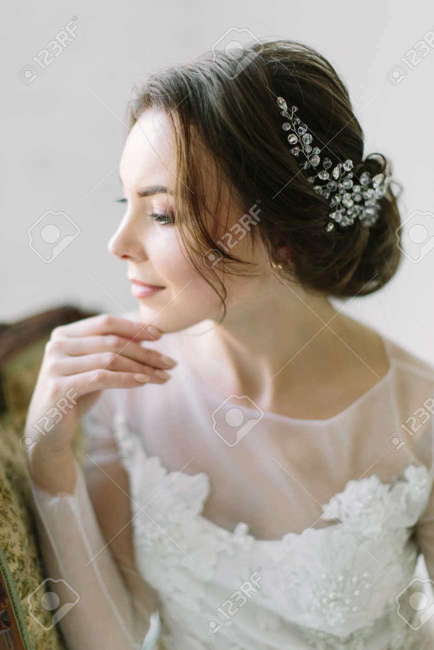 Beauty portrait of a bride with exquisite decoration in her hair, studio indoor photo. - 136361838
