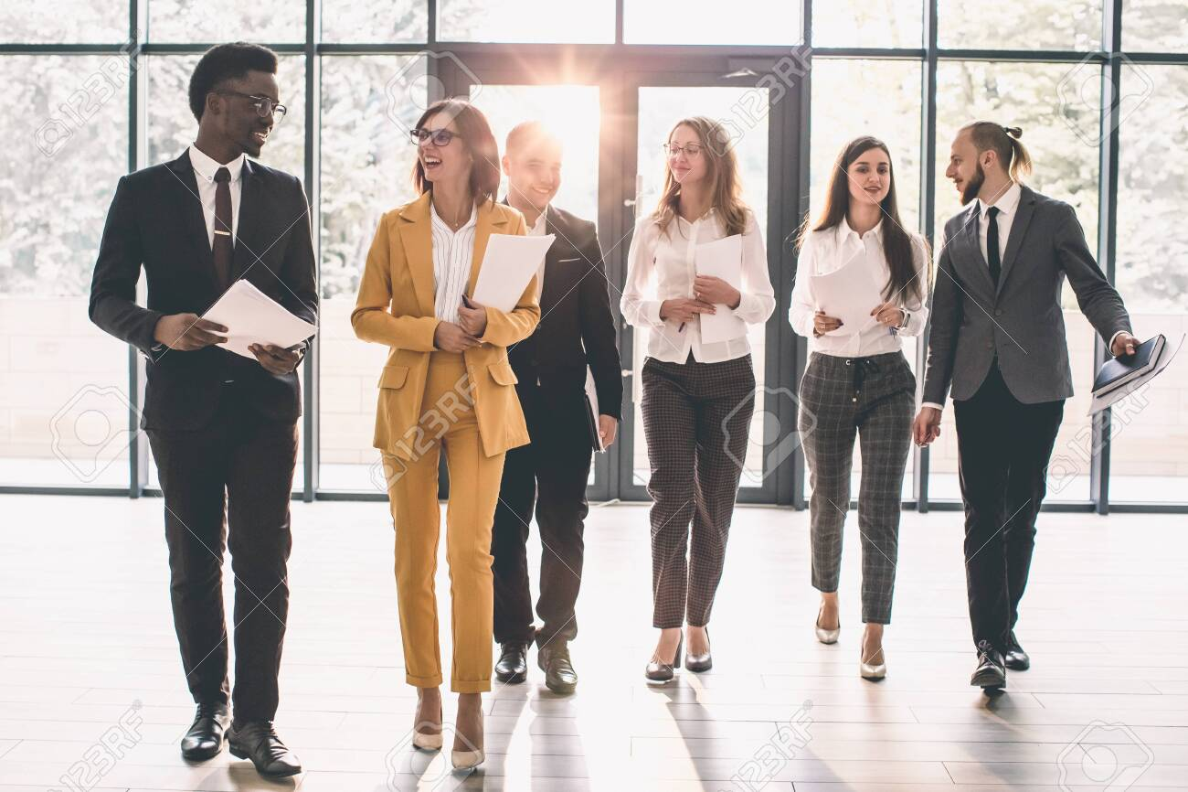 Business People Walking Toward Camera. Full length of group of happy young business people in formal wear having work meeting in modern office with large window - 141221292
