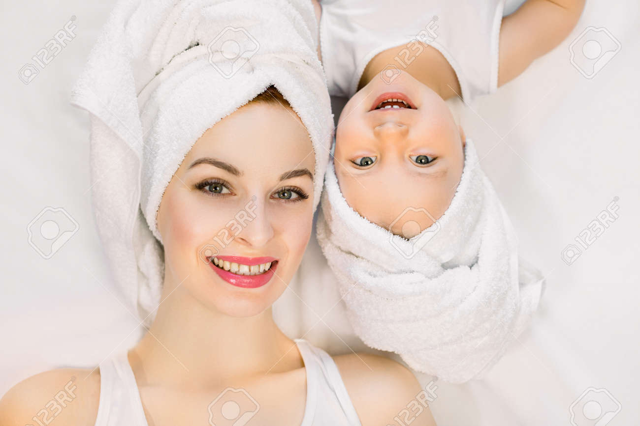 Smiling mother and daughter lying on white background, bathtime concept. Pretty young woman with little girl wearing towels on head after shower lying down and looking at camera on isolated background - 144479005