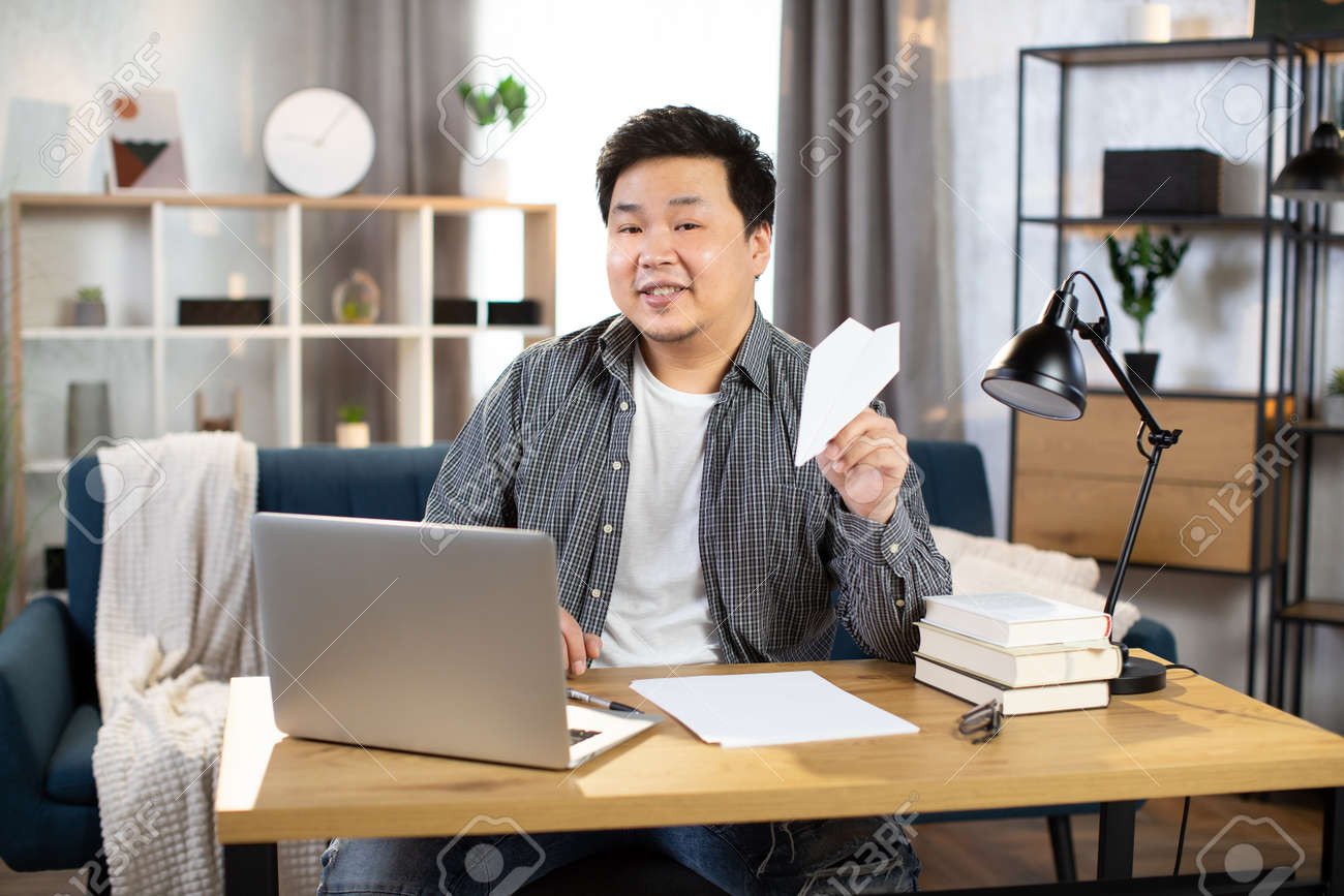 Smiling asian freelancer playing with paper plane - 166159608