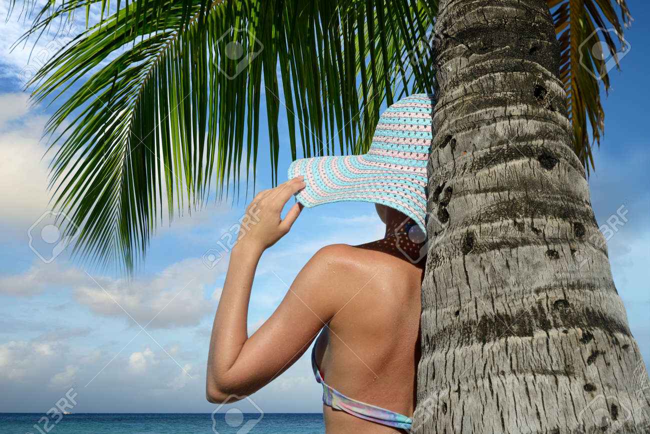 Woman under a palm tree watching the ocean dream. Stock Photo - 19135636