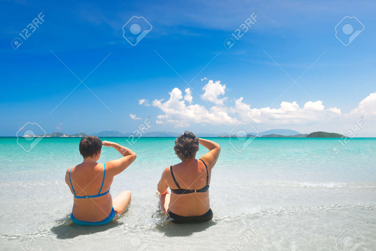 Two mature woman in swimwear relaxing on the beach and enjoying