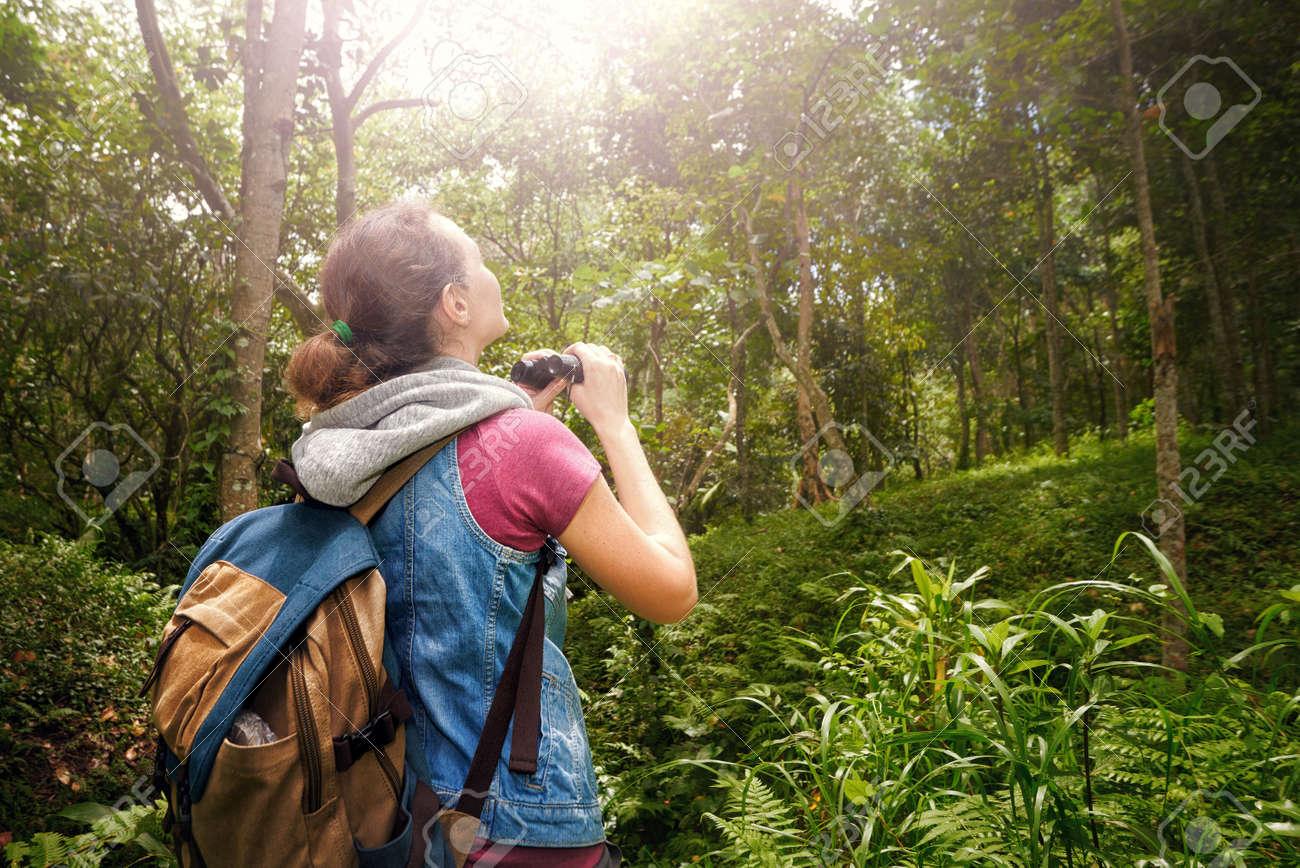 Frau wanderer beobachten durch fernglas wilde vögel im regenwald