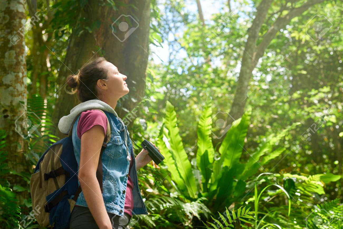 Frau wanderer durch ein fernglas wildvögeln in den tropischen