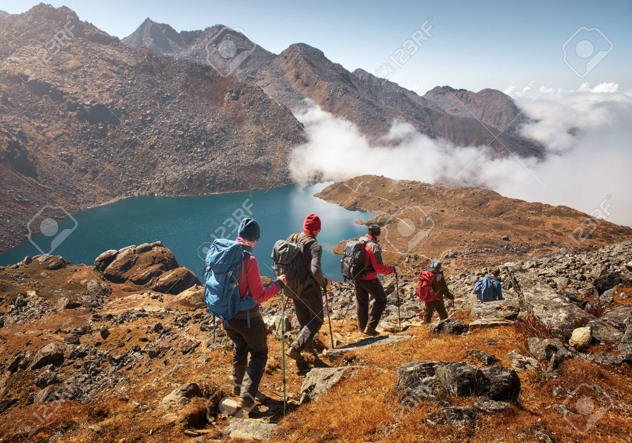 Group of tourists with backpacks descends down mountain trail to lake during a hike in the national park Lantang, Nepal.Beautiful inspirational landscape, trekking and activity. - 90745532