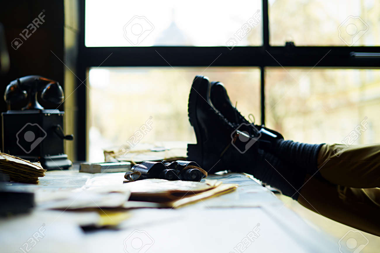 Stock Photo   View On A Desk In A Old Military Office. A Stack Of Old  Letters Tied With Laces, Old Yellow Paper, Binoculars, Telephone And Female  Legs.