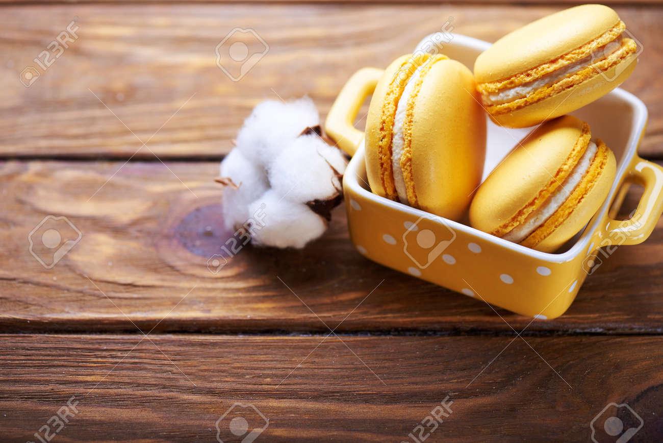 Macarons Orange En Vase Jaune Avec Des Fleurs De Coton Sur Une Table