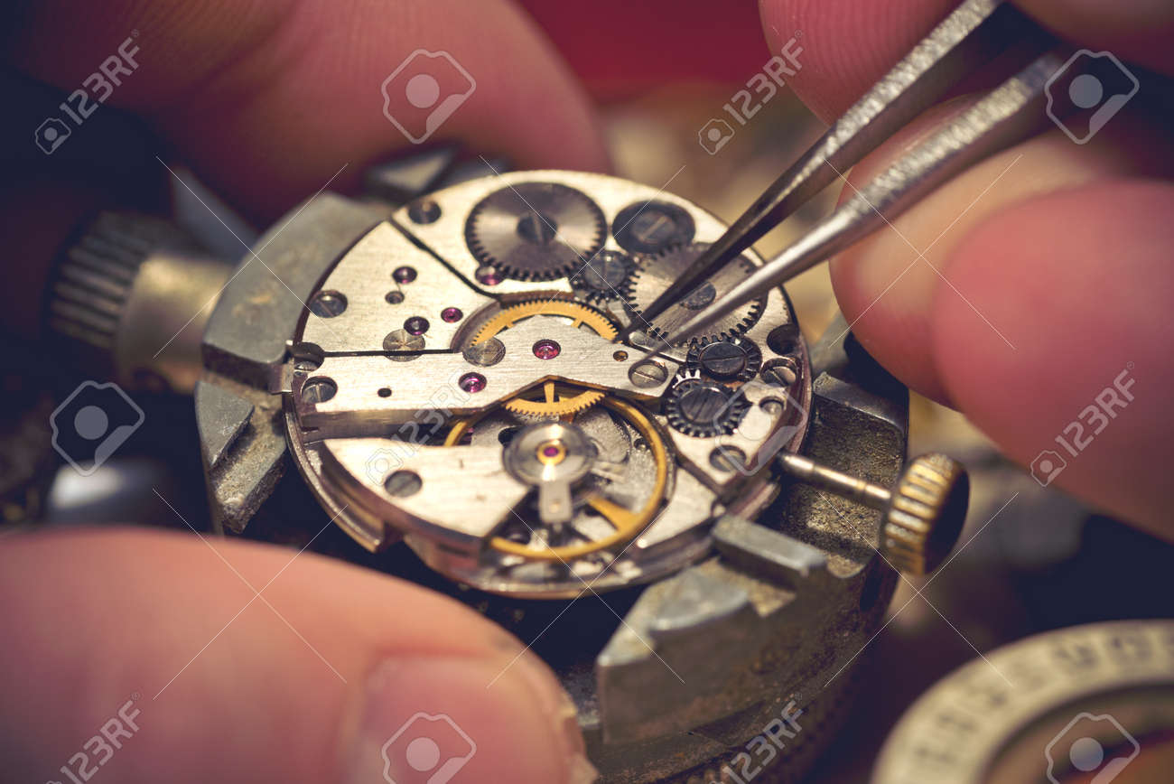 Working On A Mechanical Watch. A watch makers work top. The inside workings of a vintage mechanical watch. - 52013803