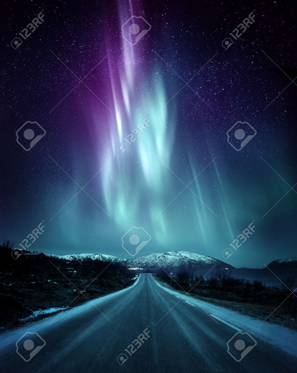 A quite road in Norway with a spectacular Northern Light Aurora display lighting up the night sky above the mountains. A popular destination within the arctic circle for hunting the Northern Lights. Photo Composite. - 110617506