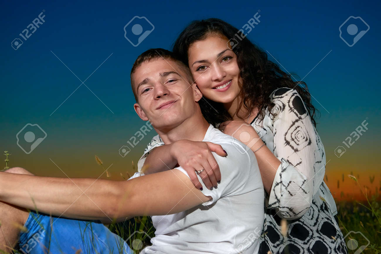 Romantic Couple Sit On Grass At Sunset Outdoor Beautiful Landscape And Dark Night Sky