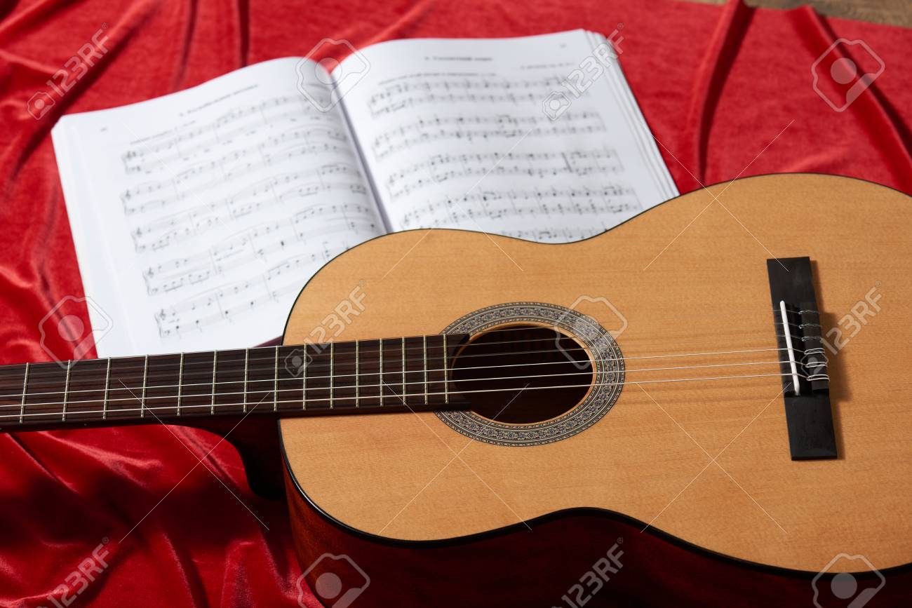 Acoustic Guitar And Music Notes On Red Fabric Close View Of Stock