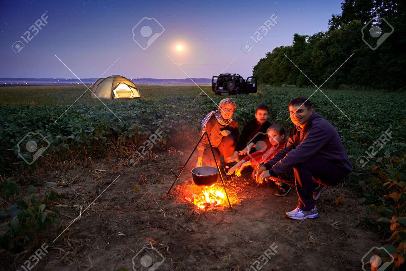 Family traveling and camping, twilight, cooking on the fire. Beautiful nature - field, forest, stars and moon. - 129641388