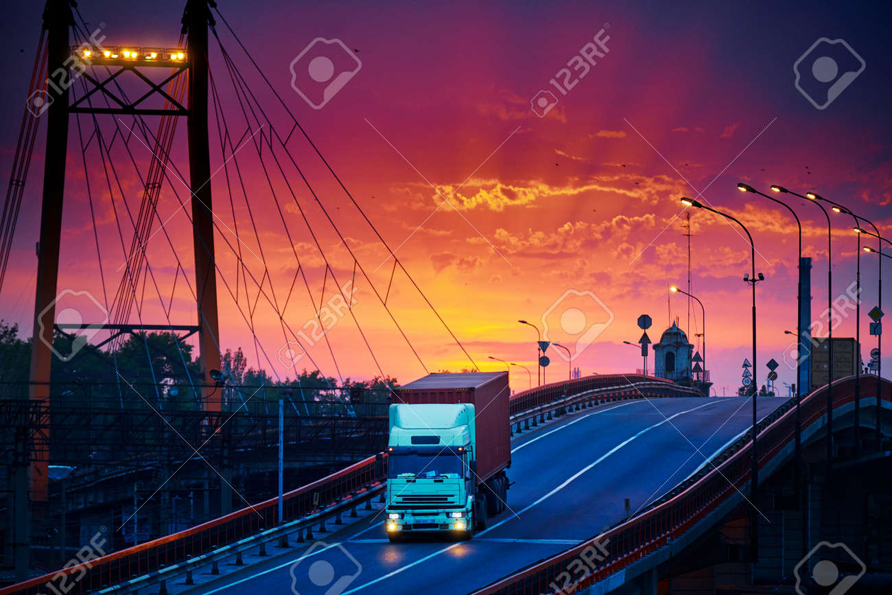 truck with container rides over the bridge, beautiful sunset, freight cars in industrial seaport, the road goes up - 135236000