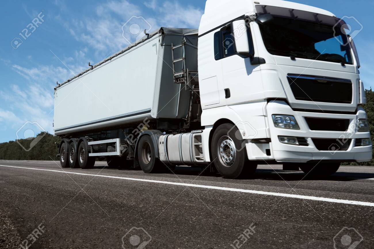 truck on the road, front view, empty space on a white container - concept of cargo transportation, trucking industry - 153028735