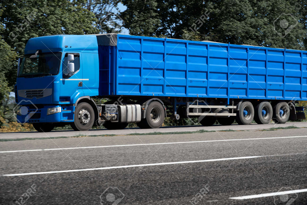 truck on the road, side view, empty space on a blue container - concept of cargo transportation, trucking industry - 153198085