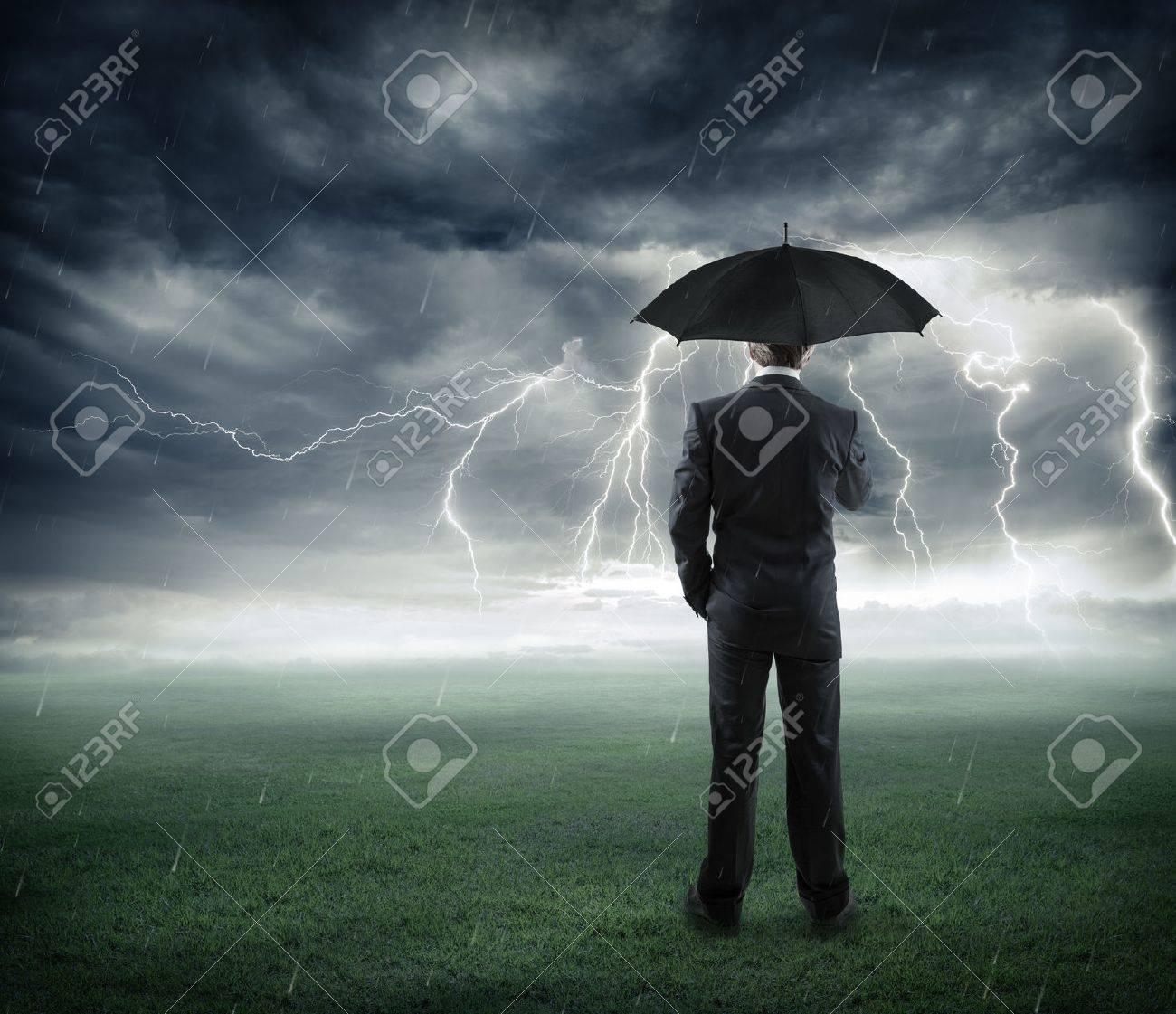 risk and crisis businessman below storm with umbrella - 41378330