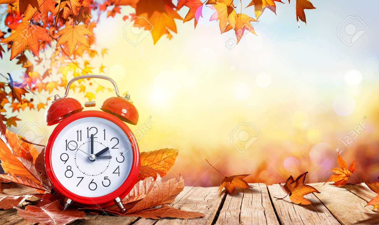 Daylight Savings Time Concept - Clock And Leaves On Wooden Table - 87701512