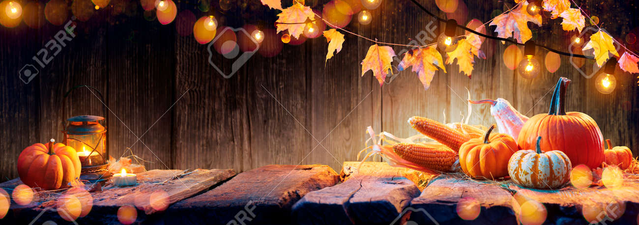 Thanksgiving Table - Pumpkins And Corncobs On Wooden Plank With Garlands - 154194342