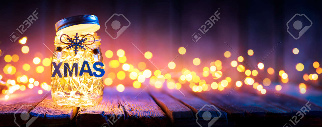 Christmas Light In Decorative Jar On wooden Table With Defocused Background - 159435978