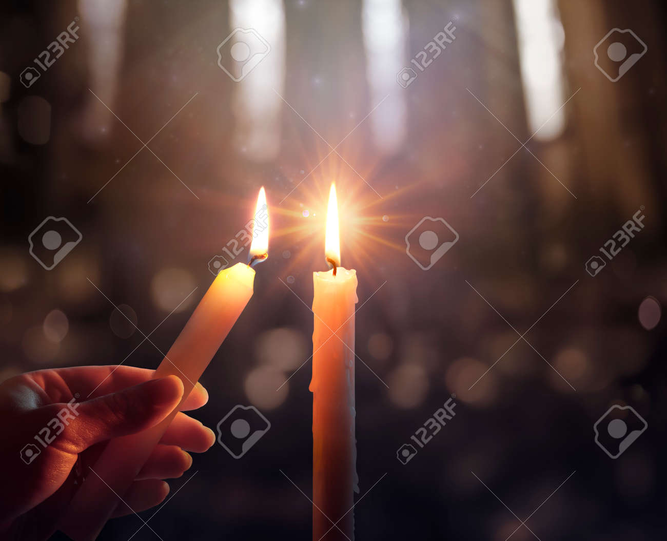 Defocused Hope Concept - Hand Igniting A Candle With Shining Flame And Blurry Lights - 160247912
