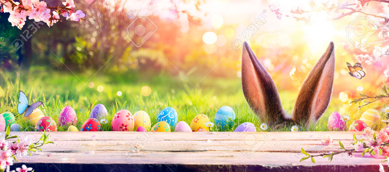 Abstract Defocused Easter Table - Ears Bunny Behind Grass And Decorated Eggs In Flowery Field - 165476447
