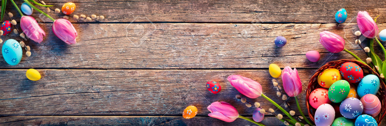 Easter Decoration - Painted Eggs In Vintage Basket On Rustic Table With Willows Branches And Tulips - 165476950