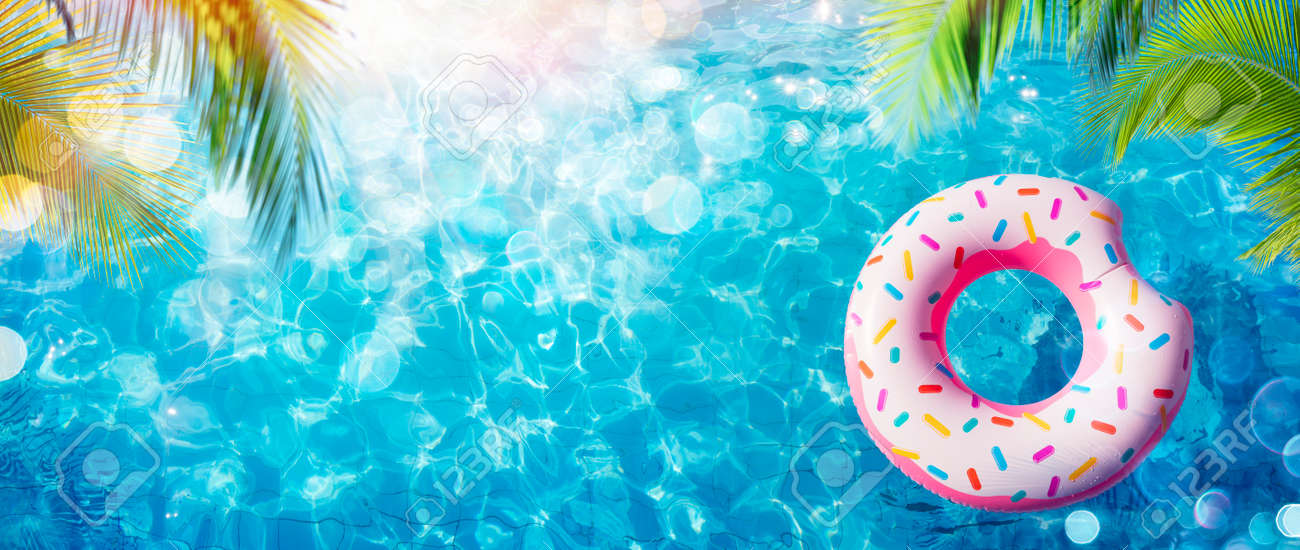 Inflatable Donut In Pool With Palm Leaves And Sunlight - 168103876