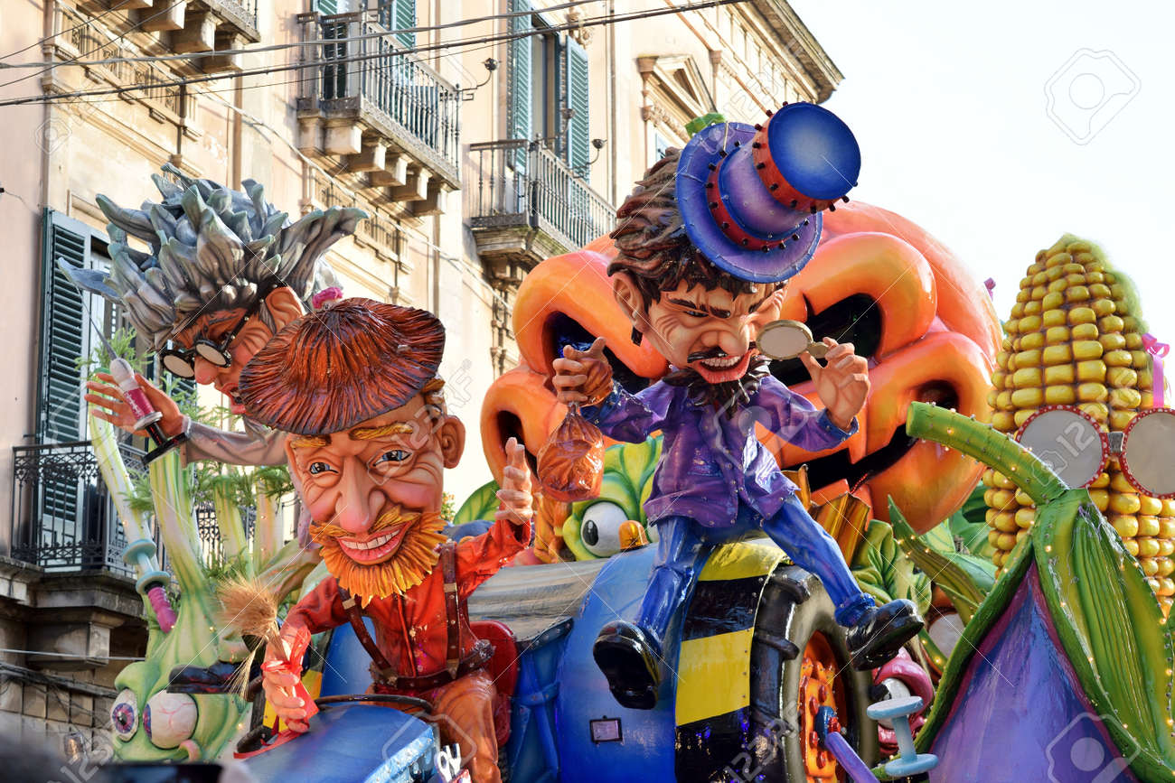 Acireale (CT), Italy - February 28, 2017: allegorical float, depicting two men with colored dress and hat one red and one purple, during the carnival parade along the streets of Acireale. - 73238213