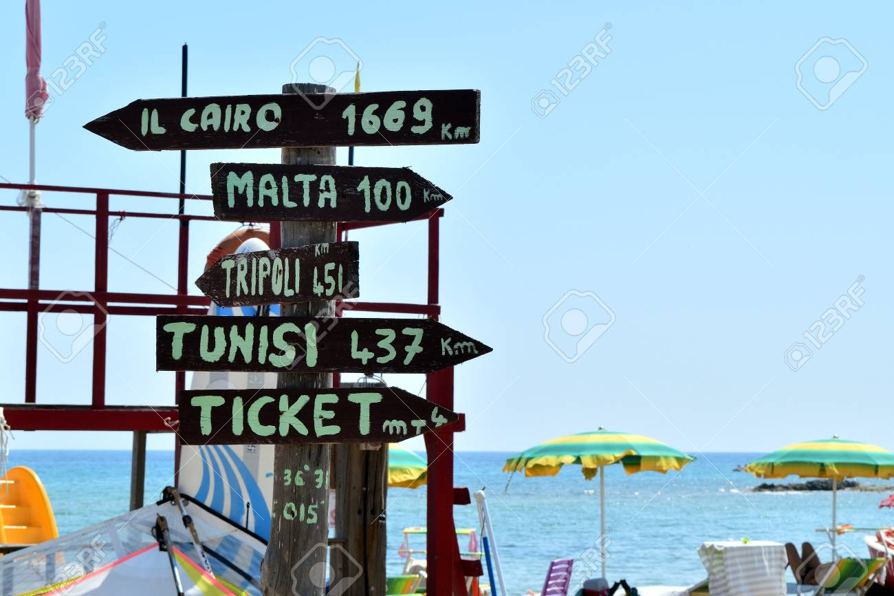 Multidirectional sign with mileage to distant cities and ticket office - 98917405