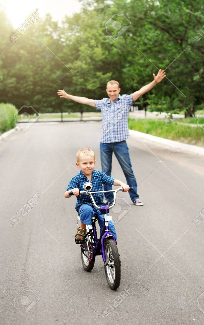 Happy father is train his son to ride a bicycle Stock Photo - 13836818