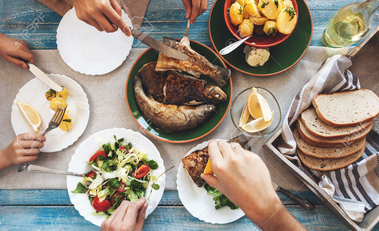Family dinner with fried fish, potato and salad - 52180516