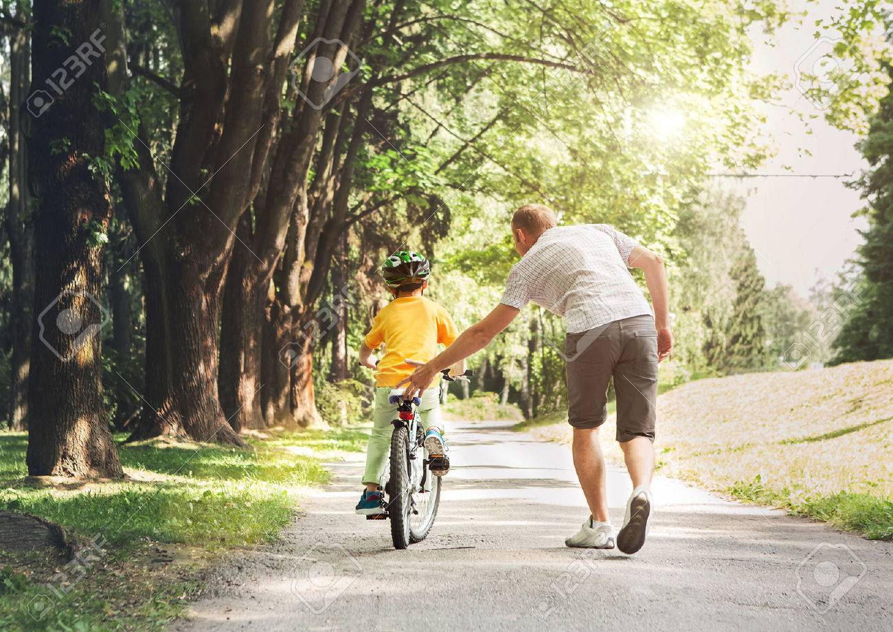 Father help his son ride a bicycle - 54668941