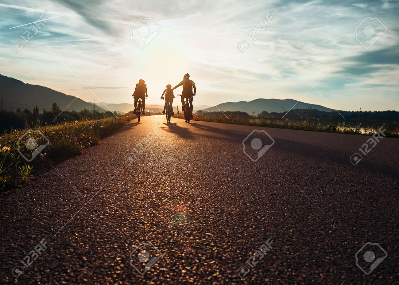 Ð¡yclists family traveling on the road at sunset - 65053758