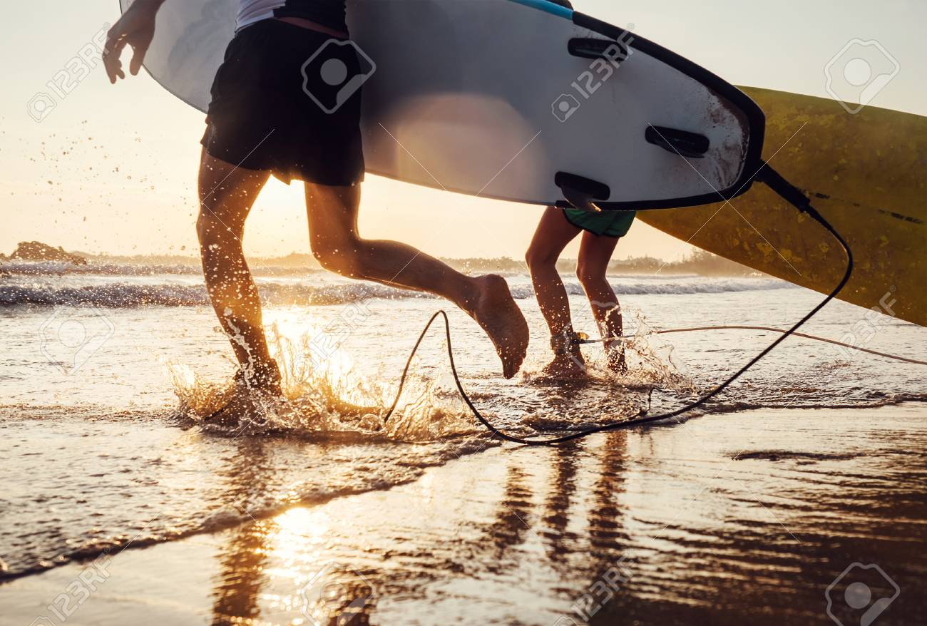 Son and father surfers run in ocean waves with long boards. Close up splashes and legs image - 93250330