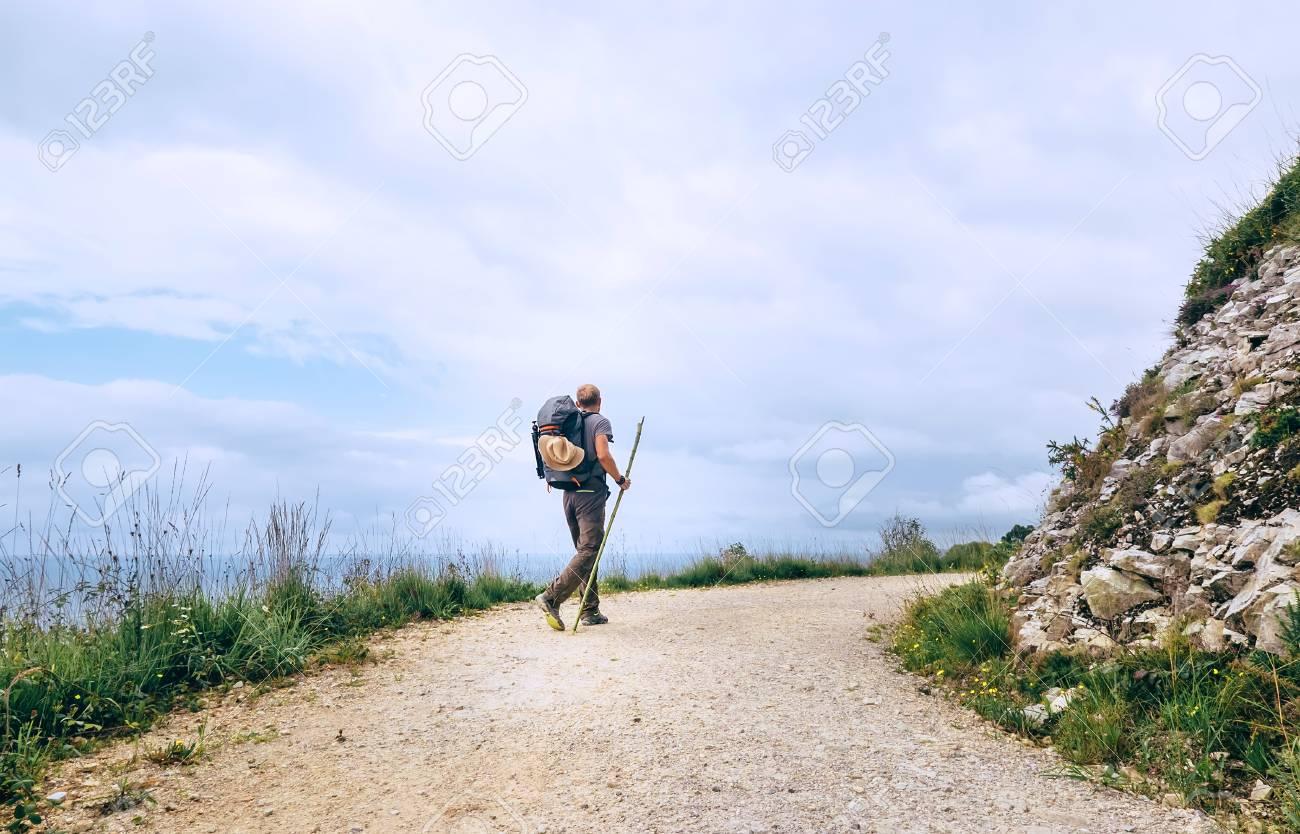 Backpacker traveler walks on road - 97064752