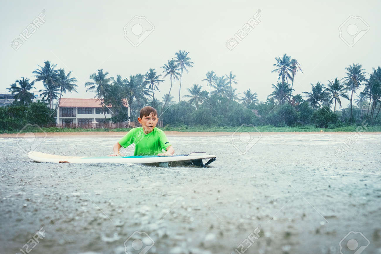 Boy Learning To Surf Under The Rain