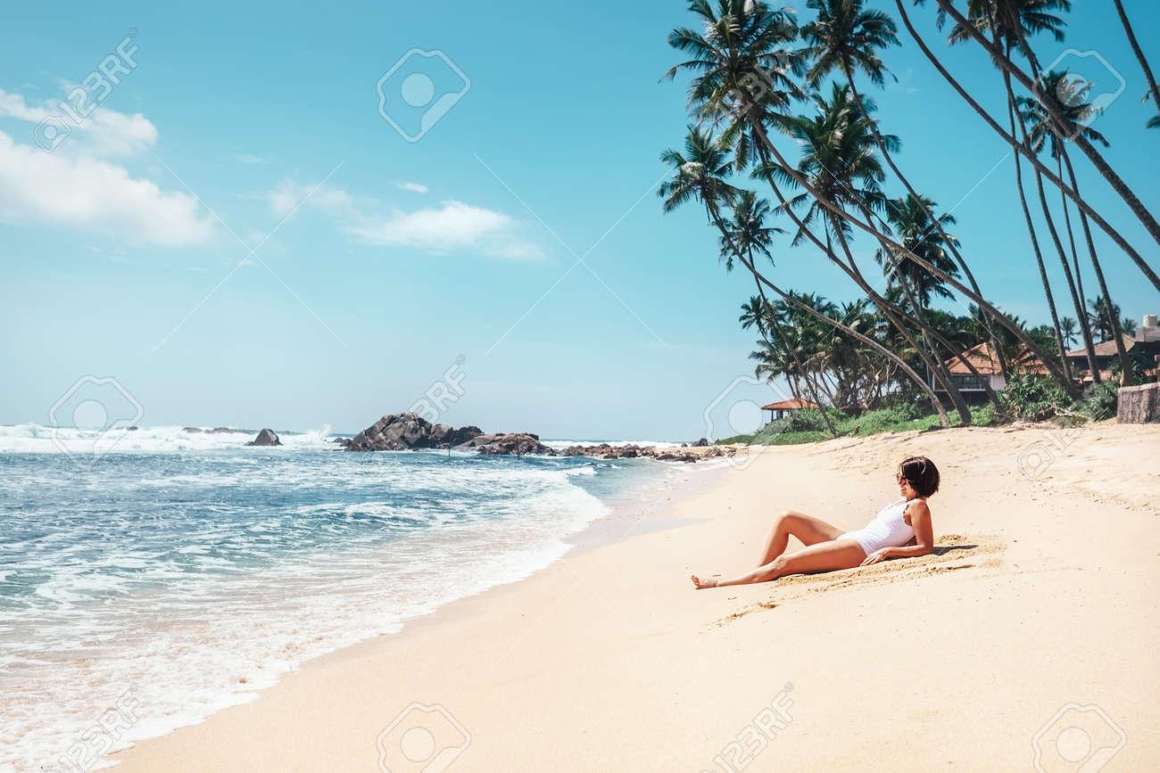 Woman takes sunbath on tropical beach. Island paradise - 104706319