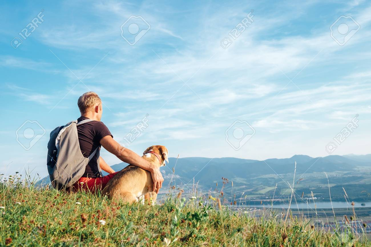 Man with his beagle dog sits on the top of hill over the mountain valley - 106895469