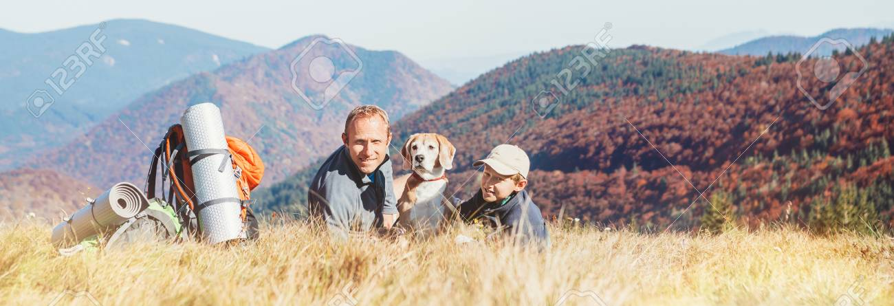 Father and son backpackers hikers rest on mountain hill with their beagle dog - 110717406