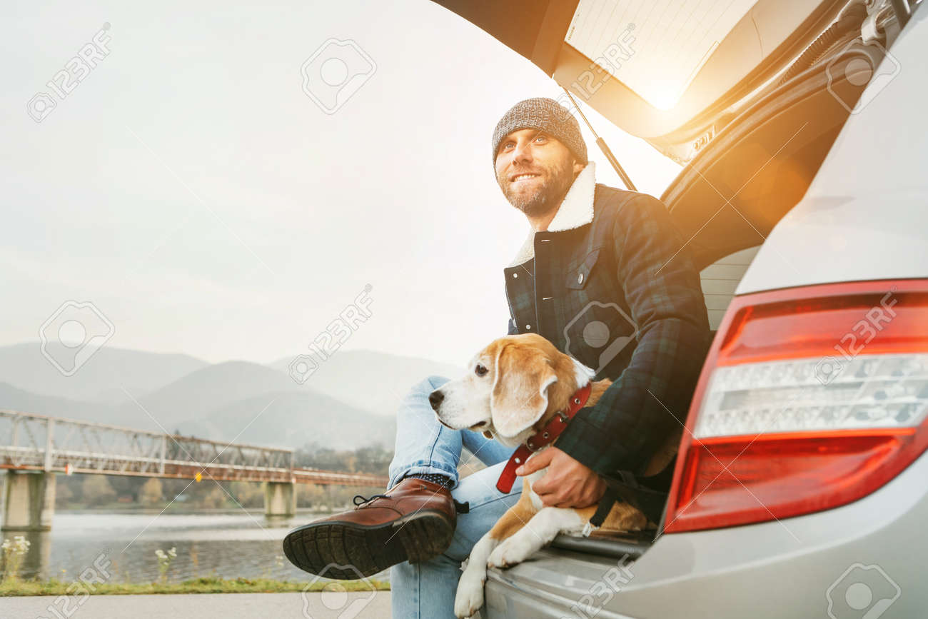 Man with beagle dog siting together in car trunk. Late autumn time - 112309090