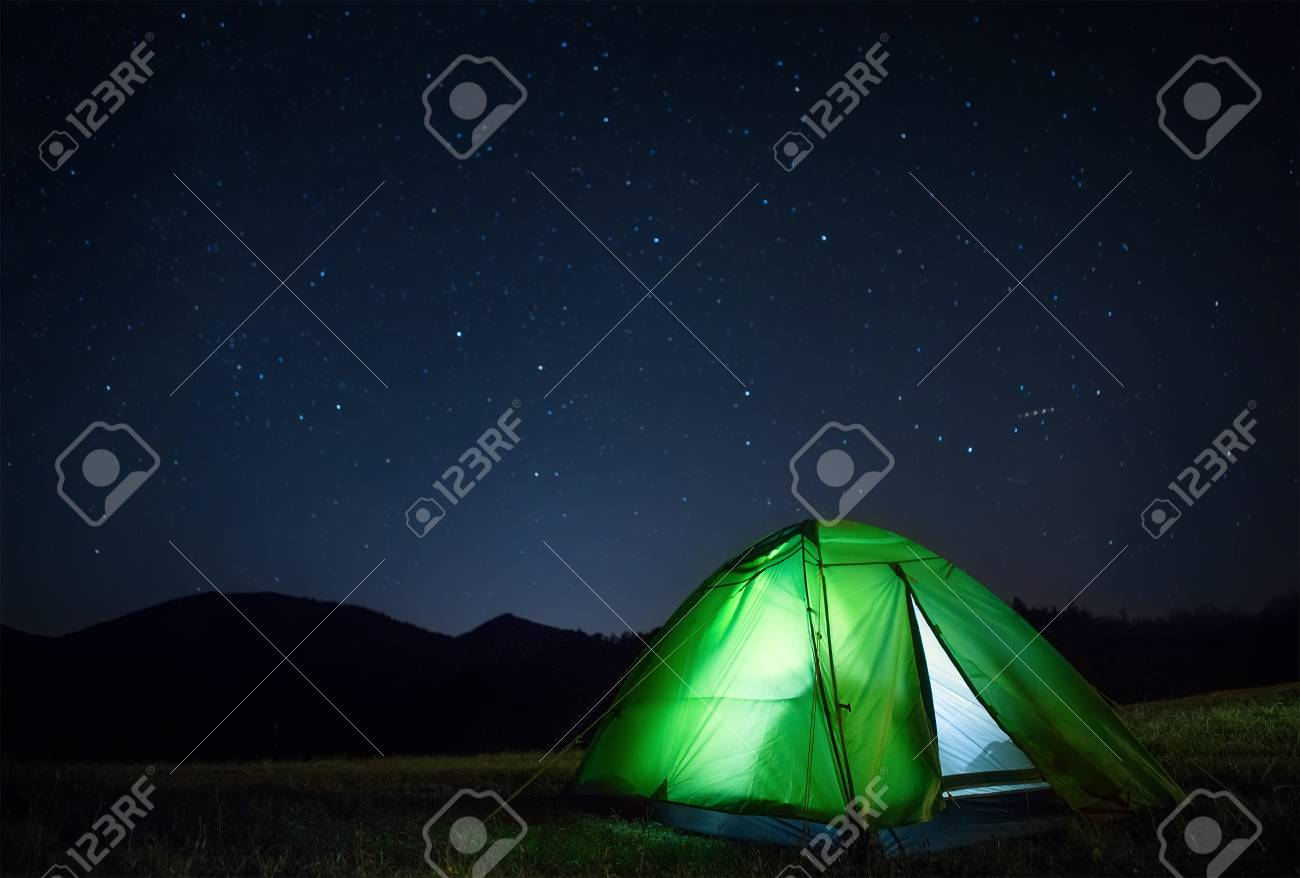Camping tent with light inside is on the mountain valley under night starry sky - 112309200