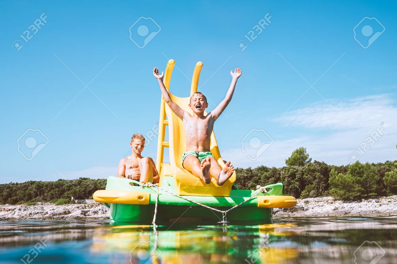 Little boy sliding down into sea water from floating Playground slide Catamaran as she enjoying sea trip with his brother - 119187919
