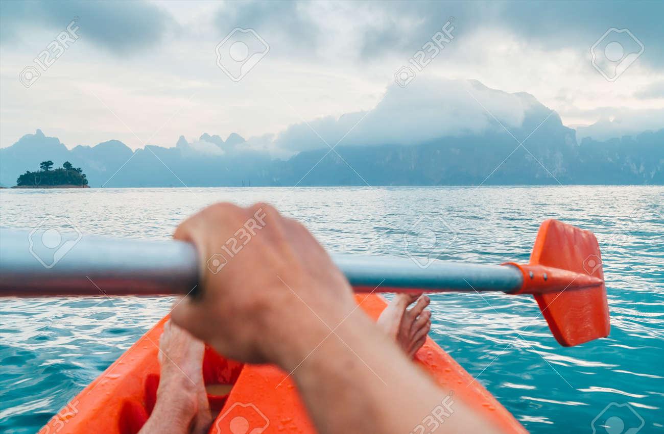 POV of Man floating in kayak holding paddle during early morning tour. Khao Sok national park, Cheow Lan lake, Thailand - 120541936