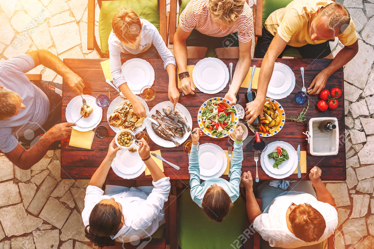Big family have a dinner with fresh cooked meal on open garden terrace - 121462490
